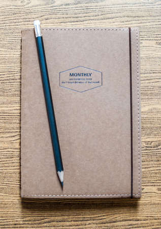 recycled paper notebook front cover on wooden background