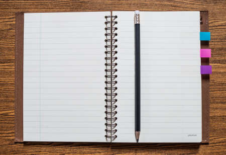 a notebook with a pencil on wooden background Standard-Bild