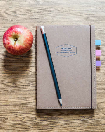 recycled paper notebook with a pencil and an apple on wooden background photo