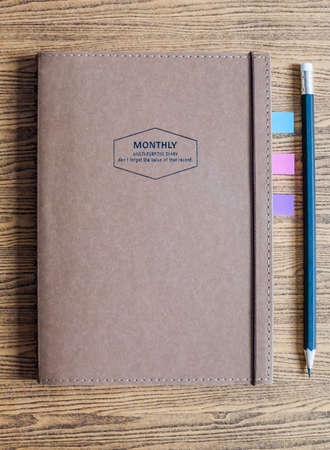 recycled paper notebook with a pencil on wooden background