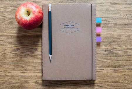 recycled paper notebook with a pencil and an apple on wooden background Standard-Bild