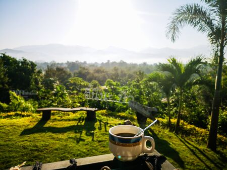 Coffee cup on balcony with nature view behind