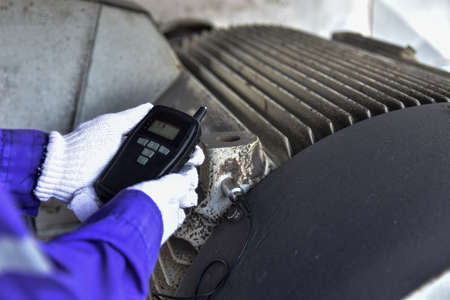 Inspector using a Handheld Vibration Tester for checking bearings and overall vibration of motor.