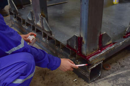 Worker are apply the penetrant to the welding of work piece with a brush for finding the defect.This is first step of Penetrant Testing (PT). Focus on the inspection area.