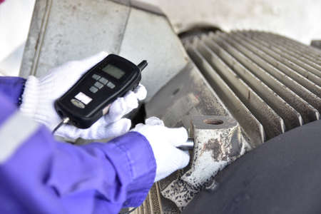 Inspector using a Handheld Vibration Tester for checking bearings and overall vibration of motor. Selective focus on inspection area. Stock fotó