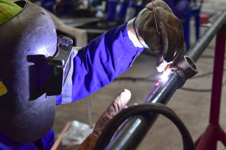 The welder is welding the pipeline with Tungsten Inert Gas Welding process (TIG). The welder wears protective equipment with a mask and heat resistant gloves