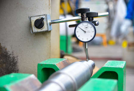 Technician measuring shaft run-out by Dial Gauge. Metal shaft put on the green support.