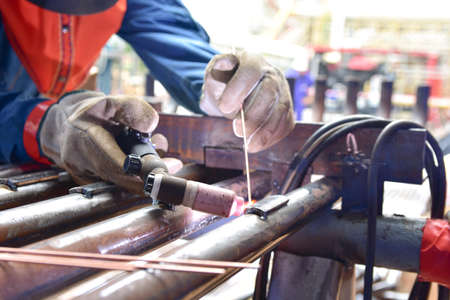 The welder is welding the plate to the pipe with Tungsten Inert Gas Welding process (TIG). The welder wears protective equipment with a mask and heat resistant gloves Banque d'images