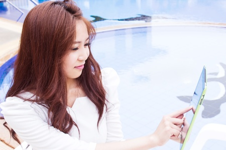 Beauty Girl Using Tablet Pc At Pool photo