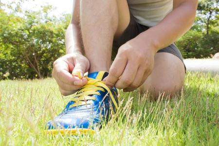 Man lacer leurs souliers sur l'herbe verte Banque d'images