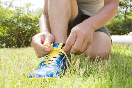 Man Tying Shoes On Green Grass Stock Photo