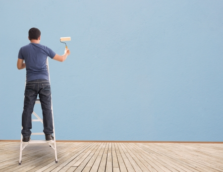 wall painting: Man Painting On Blue Wall,Concept And Ideas Stock Photo