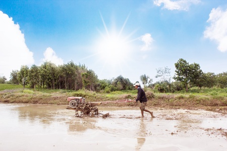 Thai Farmer Using Walking Tractors To Cultivate Soil For Rice Planting