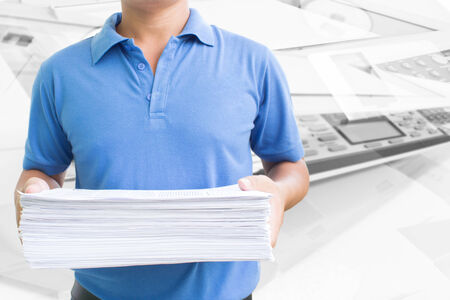 Man Carrying Pile Of Paperwork In Office  photo