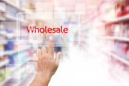 Hand Clicking On Wholesale Screen With Supermarket Shelves Blurred Background