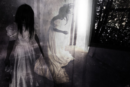恐怖の夜、お化け屋敷で幽霊、ハロウィーンのコンセプトと本のアイデアをカバーするため放棄建物、ホラー背景に立っている白いドレスで神秘的