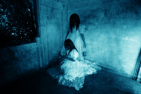 Me and My Sister,Ghost in Haunted House,Mysterious Twins Woman in White Dress Standing and Sitting in Abandon Building,Horror Background For Halloween Concept and Book Cover Ideas Archivio Fotografico