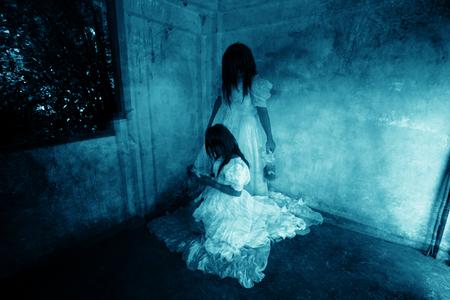 gemelas: Yo y mi hermana, Fantasma en la casa encantada, misterioso Mellizos Mujer en pie vestido de blanco y sentado en abandonar Building, Horror Fondo para el concepto de Halloween y Cubierta del libro Ideas Foto de archivo