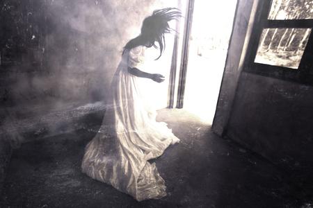 お化け屋敷で幽霊、ハロウィーンのコンセプトと本のアイデアをカバーするため放棄建物、ホラー背景に立っている白いドレスで神秘的な女性