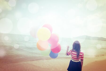 freedom concept: Woman with colorful Balloons on the beach,Outdoors lifestyle filters images