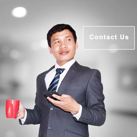 contact us sign: Asian businessman with cup of coffee and using smartphone looking away on contact us sign Stock Photo
