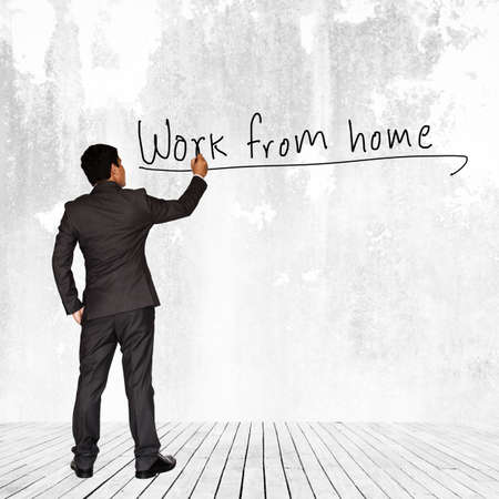 work from home: Asian businessman writing Work from home text on wall background