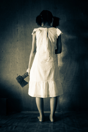 axe girl: Ghost girl in haunted house,Mysterious girl in white dress standing in abandon house carrying an axe in front of the wall