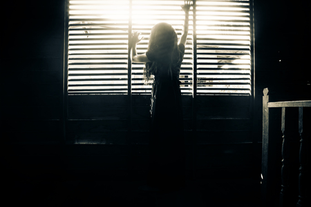 niña fantasma de la casa encantada, misteriosa chica en vestido negro de pie en abandonar la casa de la mano en la ventana Foto de archivo