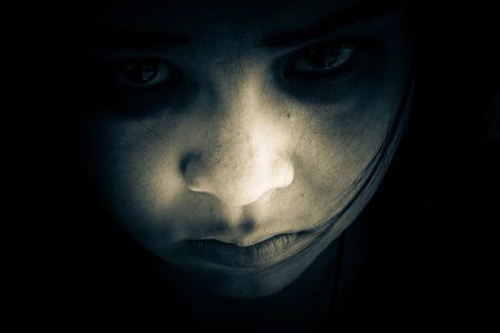 うち暗い、怖い女の子、カメラを見つめての肖像画からゴーストの暗闇の中、ハロウィーンの恐怖の背景に隠れている女の子