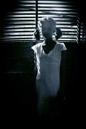 Porträt von scary Mädchen an Kameras starren, versteckt Geist Mädchen in der Dunkelheit, Grauen Hintergrund für Halloween Standard-Bild