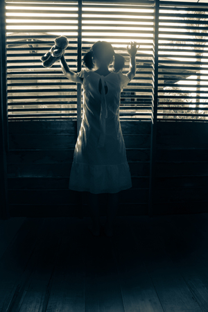 Ghost girl in haunted house,Mysterious girl in white dress standing in abandon house holding hand on the window