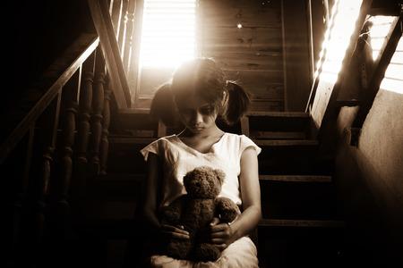 niña fantasma en la casa encantada celebración de oso de peluche, misteriosa chica en vestido blanco, sentado en la escalera de abandonar la casa Foto de archivo