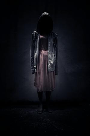 Anónimo, la mujer llevaba sudadera con capucha de pie en la oscuridad, Fondo asustadizo de la portada del libro Foto de archivo