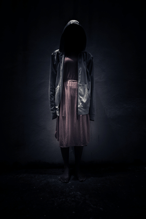 Anonyme, Femme portant un sweat à capuche debout dans le noir, Fond effrayant pour couverture de livre Banque d'images