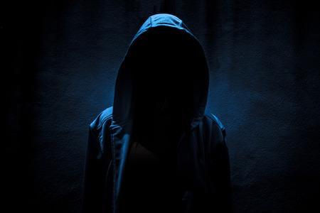 La mujer llevaba escondite con capucha en el fondo oscuro, asustadizo por la portada del libro Foto de archivo