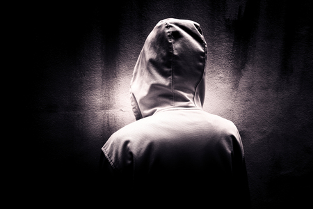 Back side of mysterious woman wearing hoodie hiding in the dark,Scary background for book cover Stock Photo