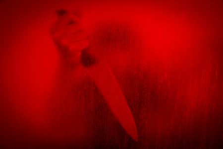 Horror scene of woman with knife behind stained or dirty window glass,Serial killer or violence concept background Stock Photo