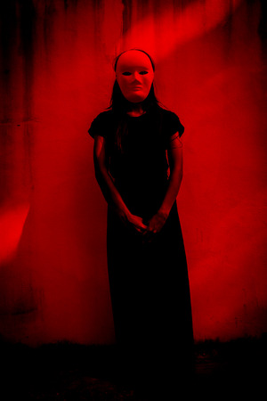 Mysterious woman in black dress wearing white mask,Scary background for book cover
