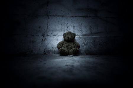 お化け屋敷の本の表紙の怖い背景に座っているクマのぬいぐるみ