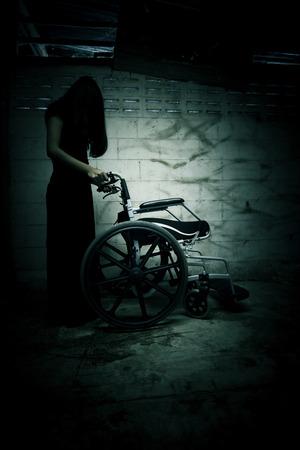 Esprit femme avec fauteuil roulant dans l'asile, fond effrayant pour la couverture du livre
