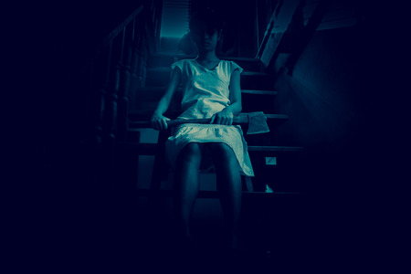 axe girl: Ghost girl in haunted house holding an axe,Mysterious girl in white dress sitting on stairway in abandon house Stock Photo