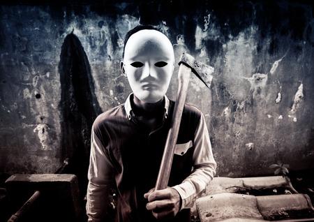 A stranger wearing white mask holding hatchet,Scary background for book cover Reklamní fotografie