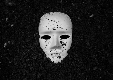 white mask: White mask in soil,Horror background for Halloween concept and book cover ideas Stock Photo