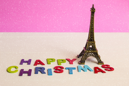 newyears: Christmas ornament with Eiffel tower on wooden background with Happy christmas text and snow Stock Photo