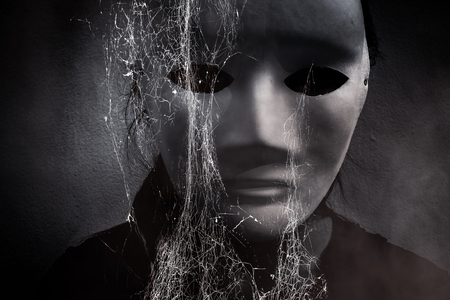 doctrine: Mysterious woman in black wearing white mask hidden behind spider web,Scary background for book cover