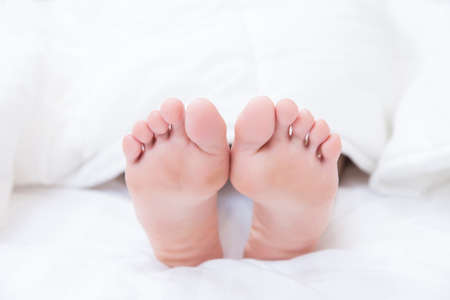 woman feet on bed