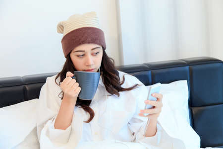Cheerful young woman sitting in bed texting on her smartphone and drinking coffee at home in bedroom Stock Photo