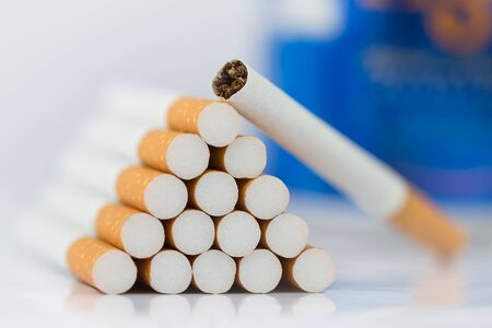 A lot of cigarette close-up The cigarette end or cigarette end is brown and the tip is white. Arranged in a triangle and there are blue beer cans on the back On a white background