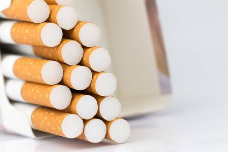 Cigarettes packed in red paper envelopes The cigarette end or cigarette end is brown and the tip is white and the end of the cigarette or cigarette end extends beyond the package on the white surface.