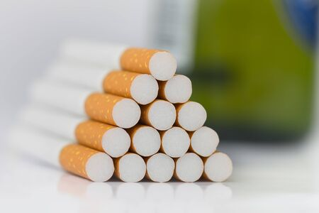 Closeup of many cigarettes The cigarette end is brown and the tip is white. Arranged in a triangle And there is a green beer bottle on the back On a white background On a white background 版權商用圖片